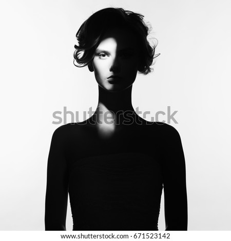 Black and white art fashion surrealistic portrait of beautiful woman with a beam of light on her face