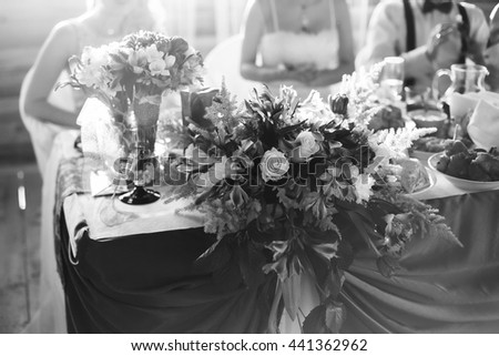 black and white art photography monochrome, wedding accessories, wedding preparation, decorated wedding table with flowers, wedding flowers, food on the table, people sitting at the table - stock photo