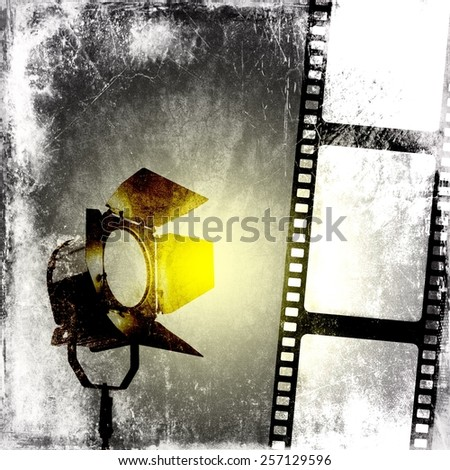 Black and white background with film strip and reflector - stock photo