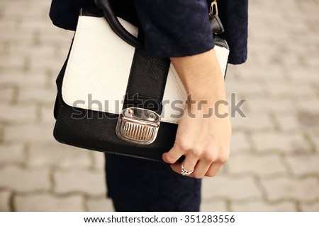 Black and white bag briefcase. Female hand on a black and white purse. Close-up. Woman on a walk. Business style, a style element, accessory. - stock photo