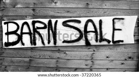 Black and white barn sale sign, spray painted on white, hanging on the side of a old barn - stock photo