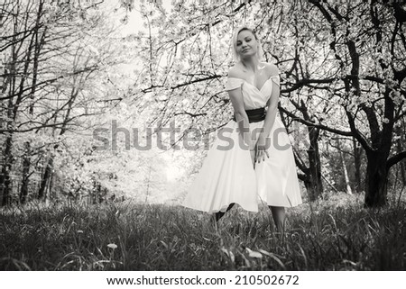 Black and white. Beautiful blonde in a garden. Girl enjoying nature. Garden, beauty, trees, - concept of enjoying nature. Idea of  the article about the garden and nature.