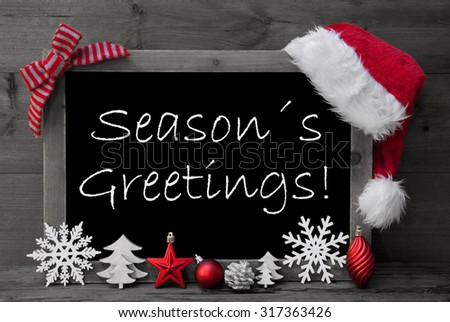 Black And White Blackboard With Red Santa Hat And Christmas Decoration like Snowflake, Tree, Christmas Ball, Fir Cone, Star. English Text Seasons Greetings. Wooden Background - stock photo