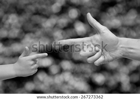 Black and white caucasian male and boy hands pointing, or gun gesture, on blurred background. - stock photo