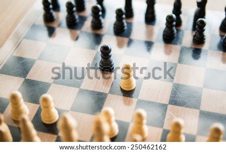 Black and white chess in the center of board, Means the competition, Shallow in depth of field - stock photo