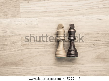 Black and white chess kings lying down. Concept of draw, competition and conflict with no winner. - stock photo