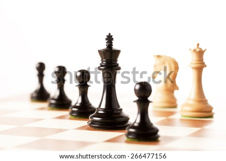 black and white chess kings with pawns standing on a chessboard in perspective  - stock photo