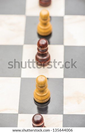 Black and white chess pawns standing in a row on chessboard - stock photo