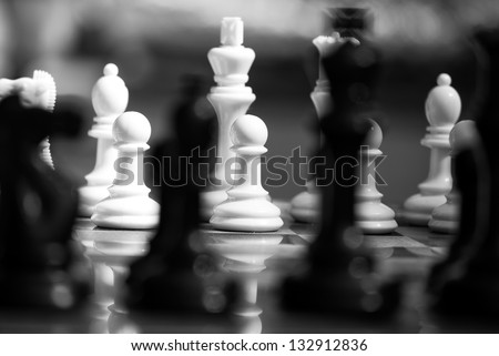 Black and white chess pieces with shallow depth of field. Abstract image. - stock photo