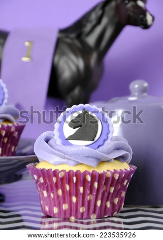 Black and white chevron with purple theme party luncheon table place setting for Melbourne Cup, Australian public holiday, horse race event cupcake - vertical closeup. - stock photo
