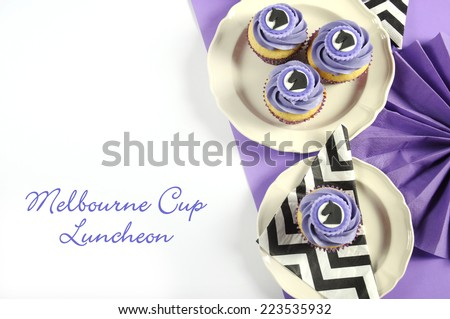 Black and white chevron with purple theme party luncheon table place setting for Melbourne Cup, Australian public holiday, horse race event cupcakes with closeup and sample text. - stock photo