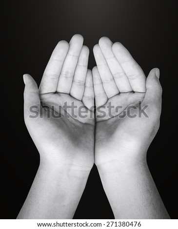 Black and white children open empty hands with palms up. Human hands of prayer in dark room background. - stock photo