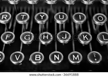 Black and white classy shot of an old typewriter's keys. Dirty and dusty and worn through lots of use since the 1900-1920s period when they were made. - stock photo