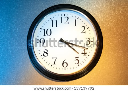 Black-and-white clock on wall with light and shade symbolizing day and night. Usual clock on two-coloured background: blue and light brown. Symbol of time passing away and future. - stock photo