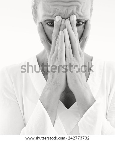 Black and white close up beauty portrait of a senior mature healthy woman with flawless skin looking worried and emotional. Mature and aging face with a sad expression, outdoors. Face in hands. - stock photo