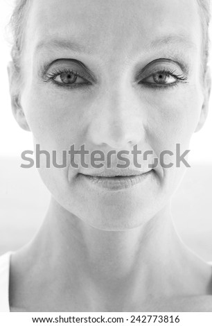 Black and white close up beauty portrait of senior mature healthy woman with light eyes and flawless skin looking at the camera. Mature and aging face with a serene and confident expression, outdoors. - stock photo
