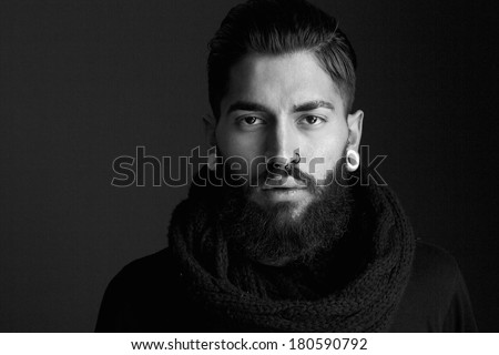 Black and white close up portrait male fashion model with beard and piercing - stock photo
