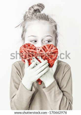 Black and white, close up portrait of five years old caucasian blond child girl holding red heart symbol on a white background. Love, Valentine's Day or charity concept. - stock photo