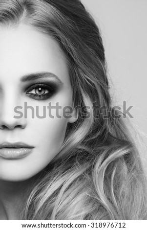 Black and white close-up portrait of young beautiful woman with smoky eyes and stylish messy hairdo