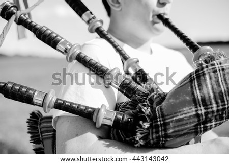 Black and white closeup of young male playing traditional Scotland bagpipe on summer outdoors background - stock photo