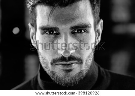 Black and white closeup photo of handsome young man looking at camera. - stock photo