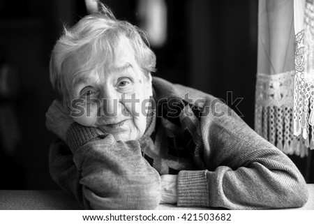 Black and white closeup portrait of an elderly woman. - stock photo