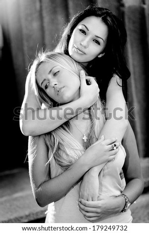 Black and white closeup portrait of two beautiful sexy girls hugging on street - stock photo
