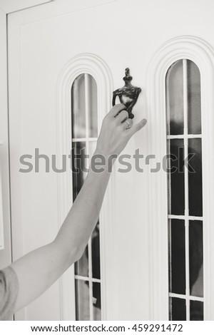 Black and white closeup view on hand on beautiful door knocker, elegant design light background - stock photo