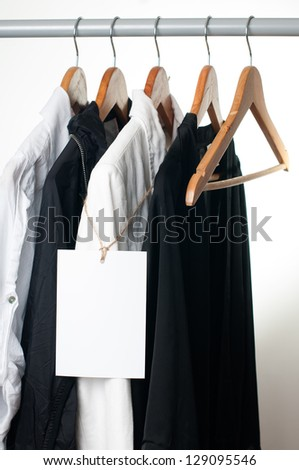 Black and white clothes hanging on a rack in a row with a blank label - stock photo