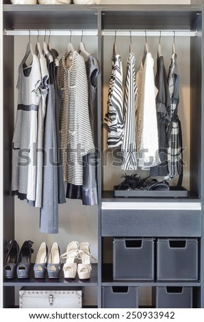 black and white clothes in black closet at home - stock photo