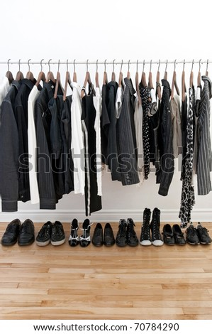 Black and white clothes on a pole and shoes on a wooden floor. - stock photo