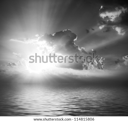 black and white cloudy sunrise (sunset) with sunbeams, clouds and reflection in water surface - stock photo
