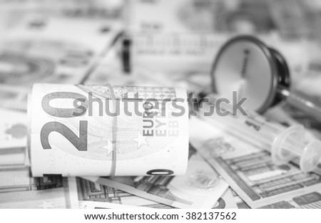 Black and white color of euro currency with blurry stethoscope and syringe costs for the medical insurance,Focus on number 20 of currency roll - stock photo