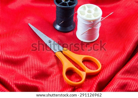 Black and white color thread with orange scissors on Red cloth - stock photo