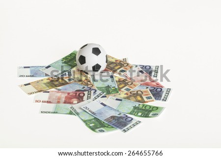 black and white colored soccer ball on a white background with euro banknotes, concept for sport and business - stock photo