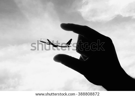 black and white conceptual image with plane and human hand - stock photo