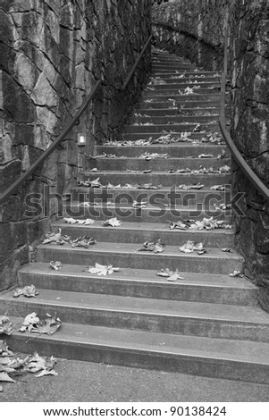 Black and White concrete stairway up a windy stone corridor - stock photo