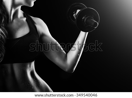 Black and white dark contrast photo of muscular arms, waist and belly with beads of sweat of young fitness woman, which training, working out with dumbbells on black background
