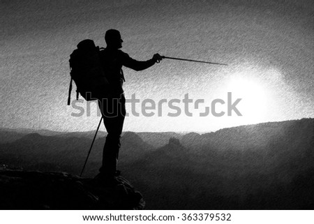 Black and white dashed retro sketch. Sharp silhouette of a tall man on the top of the mountain with sun in the frame - stock photo