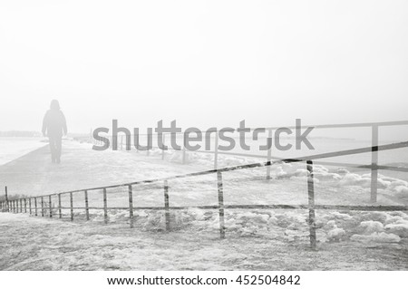 Black and white double exposure of person walking on foggy pier. - stock photo