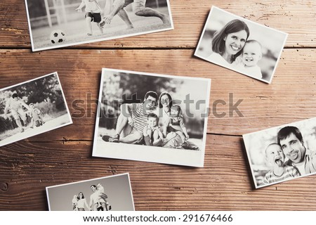 Black and white family photos laid on wooden table background. - stock photo