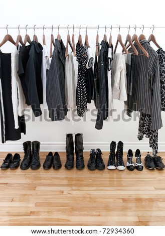 Black and white female clothes on hangers and shoes on a wooden floor. - stock photo