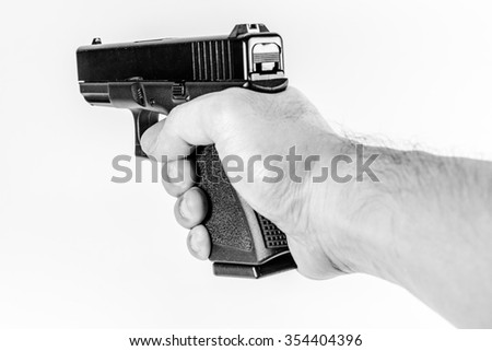 black and white filter effect photo of black color gun holding in hand isolated on white background - stock photo