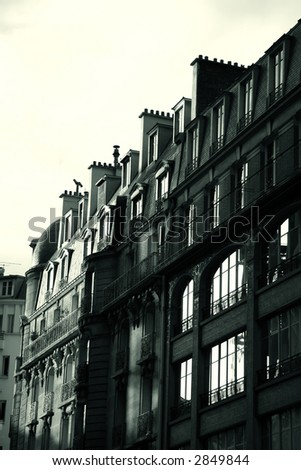 Black and white french building - sun rising on windows - stock photo