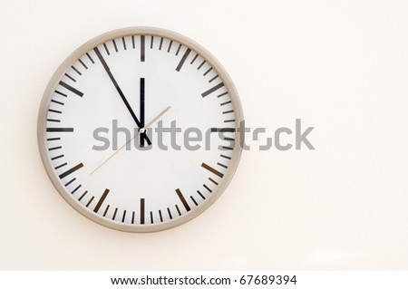 black and white generic clock showing five to twelve - stock photo