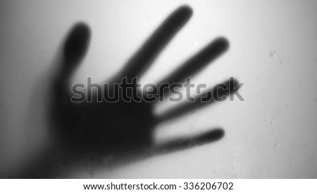 Black and White hand shadow through window glass. - stock photo