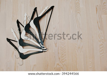 Black and white hangers on light wooden background