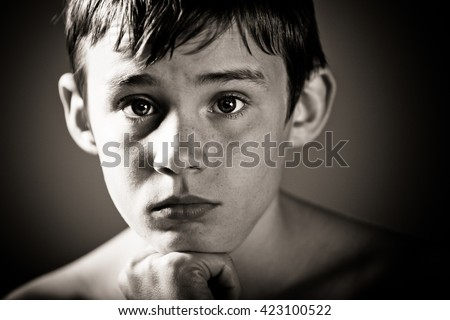 Black and White Head and Shoulders Close Up of Young Shirtless Teenage Boy Staring at Camera with Worried Expression and Chin Resting on Hand in Vignette Studio with Dark Background and Copy Space