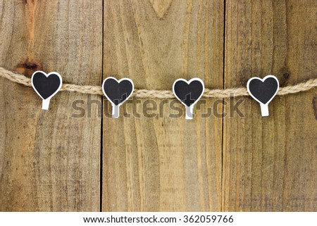 Black and white heart clothespins hanging on clothesline with antique rustic wood background; Valentine's Day - stock photo
