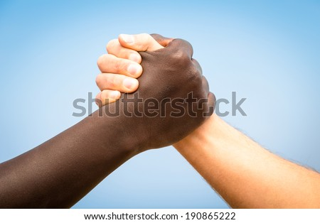 Black and white human hands in a modern handshake to show each other friendship and respect - Arm wrestling against racism - stock photo